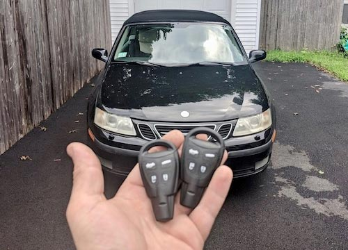 man holding two saab car key fobs in front of a saab car